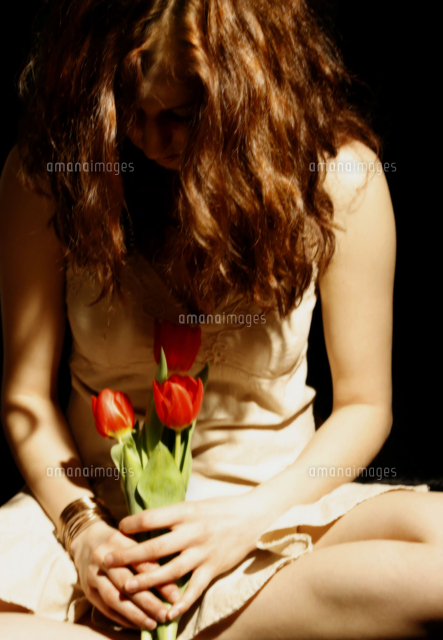 Portrait of a female seated holding red tulips