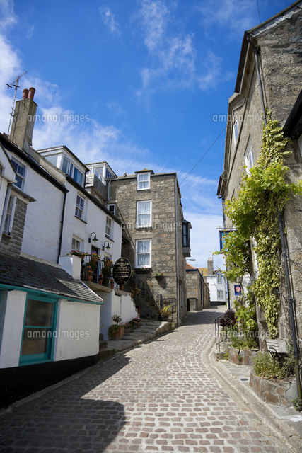 A small cobbled street in St Ives with bed and breakfast signs and blue skies.