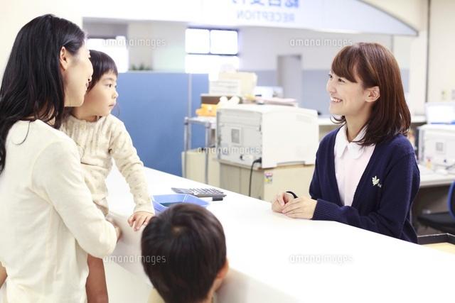 病院の受付で来院者れに対応する女性職員[10186003467]の写真素材・イラスト素材|アマナイメージズ