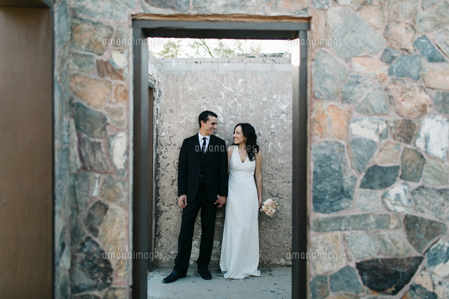 Bride and groom, outdoors, holding hands, smiling