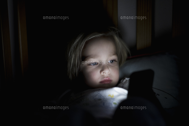 Young boy using mobile phone while lying on bed at night