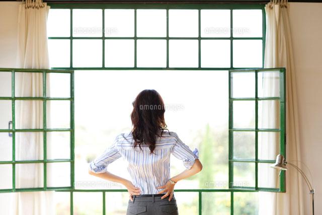 窓から外を見る女性の後ろ姿[11038001688]の写真素材・イラスト素材|アマナイメージズ