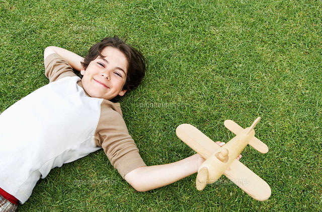 Smiling Pre-teen boy lying on back in grass  arm behind he
