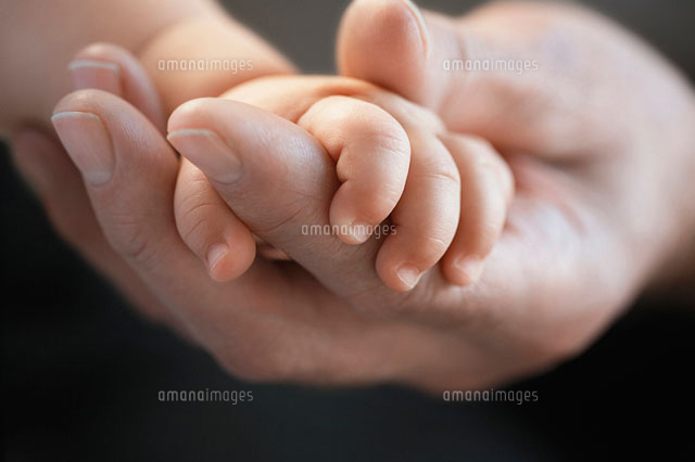 Baby holding mans finger  close up of hands