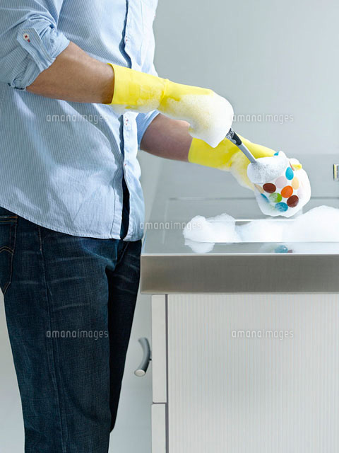 Man doing washing up at kitchen sink  mid section  side vi