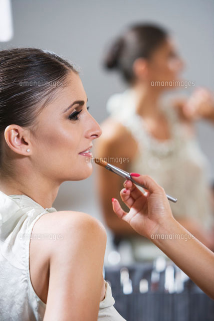 Profile of woman sitting in makeup  lip gloss application