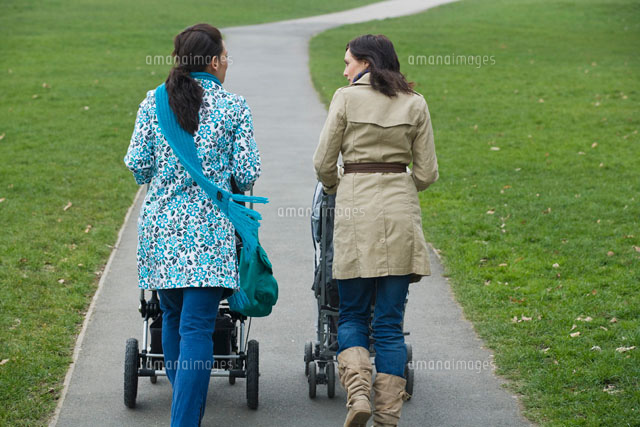Back view of two mothers pushing strollers in park