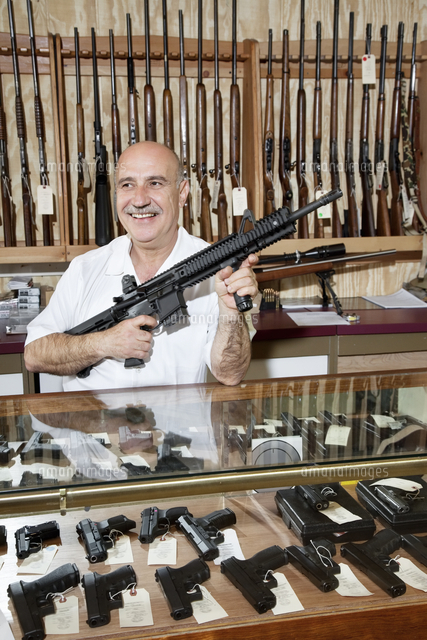 Happy mature man with rifle in gun store