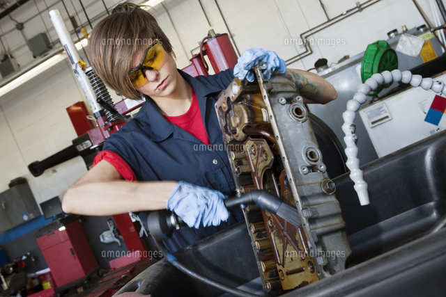 Young female mechanic working with welding torch on vehicle