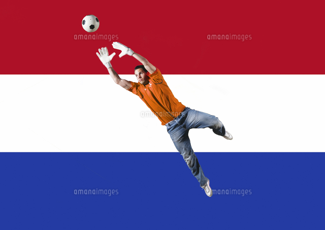 Football Goalkeeper saving shot in front of Dutch National Flag