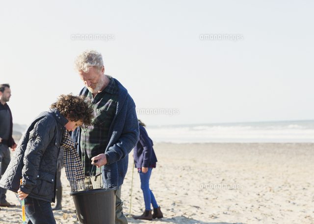 Multi-generation family clam digging on sunny beach