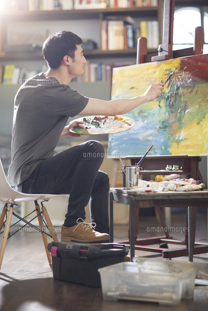 Artist painting in his studio