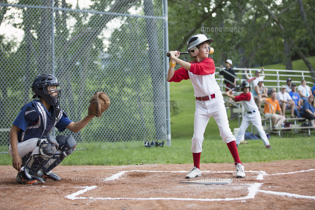 Young male baseball player ready to bat at home.