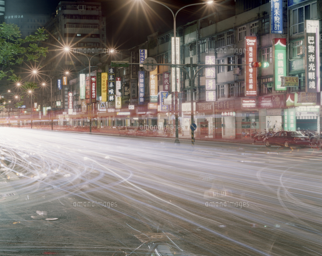 Light trails on road by buildings in city 11100047328| 写真素材・ストックフォト・画像・イラスト素材|アマナイメージズ