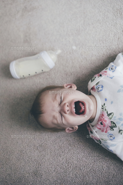 Overhead view of toddler crying while lying on floor at home