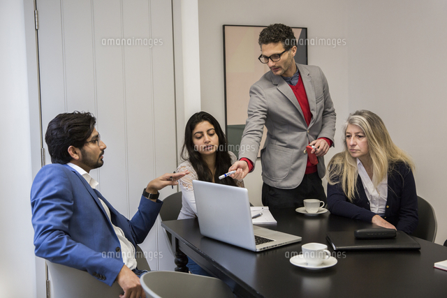 Business people discussing over laptop computer at desk in office 11100085256| 写真素材・ストックフォト・画像・イラスト素材|アマナイメージズ