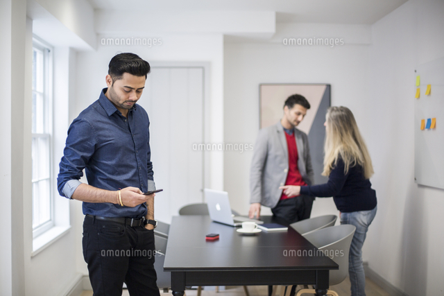 Businessman using smart phone with colleagues standing at desk in background 11100085258| 写真素材・ストックフォト・画像・イラスト素材|アマナイメージズ