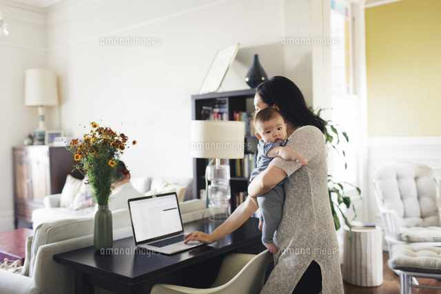 Side view of woman carrying daughter using laptop while standing at home