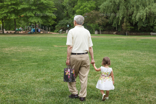 Rear view of grandfather holding granddaughter's hands while walking on grassy field at park