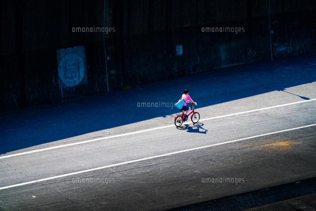 High Angle View Of Woman Riding Bicycle On Road 11115152356| 写真素材・ストックフォト・画像・イラスト素材|アマナイメージズ