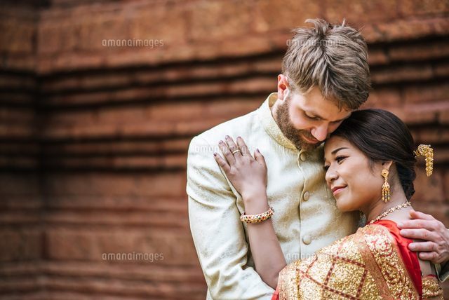 Couple Embracing While Standing Against Building