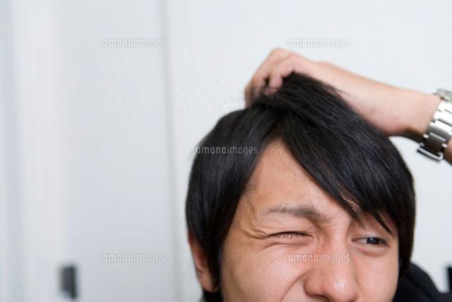 頭を掻く男性 の写真素材 イラスト素材 アマナイメージズ