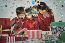 Surprised brothers and sisters unwrapping glowing christmas gift box with exploding confetti 11015246870| 写真素材・ストックフォト・画像・イラスト素材|アマナイメージズ