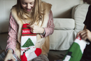 Two people unwrapping Christmas stocking presents on Christmas morning.  11093009289| 写真素材・ストックフォト・画像・イラスト素材|アマナイメージズ