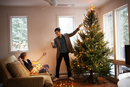 Young couple decorating Christmas tree in living room 11100005670| 写真素材・ストックフォト・画像・イラスト素材|アマナイメージズ