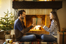 Happy couple holding Christmas present by fireplace at home 11100048359| 写真素材・ストックフォト・画像・イラスト素材|アマナイメージズ