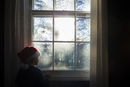 Boy in Santa hat looking through window while standing at home 11100049052| 写真素材・ストックフォト・画像・イラスト素材|アマナイメージズ
