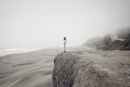 Side view of woman standing on cliff at beach during foggy weather