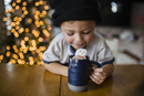 Happy boy looking in cup with marshmallow snowman at home 11100053387| 写真素材・ストックフォト・画像・イラスト素材|アマナイメージズ