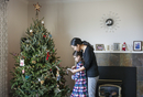 Side view of woman with daughter decorating Christmas tree at home 11100054944| 写真素材・ストックフォト・画像・イラスト素材|アマナイメージズ