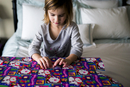 Girl wrapping gift box while sitting on bed 11100057689| 写真素材・ストックフォト・画像・イラスト素材|アマナイメージズ