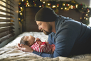 Side view of father with baby girl on bed at home 11100057715| 写真素材・ストックフォト・画像・イラスト素材|アマナイメージズ