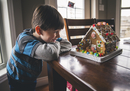 Happy boy looking at gingerbread house on wooden table during Christmas