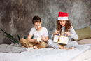 Sibling Opening Christmas Present While Sitting On Bed At Home 11115170909| 写真素材・ストックフォト・画像・イラスト素材|アマナイメージズ