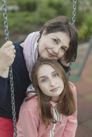Portrait of senior woman with granddaughter on swing at playground