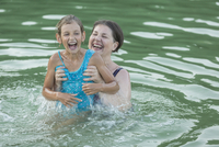 Smiling grandmother enjoying with granddaughter while swimming in pool