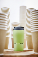Green insulated drink container surrounded by disposable coffee cups 11086040126| 写真素材・ストックフォト・画像・イラスト素材|アマナイメージズ