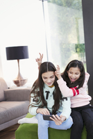 Playful sisters taking selfie with smart phone in living room