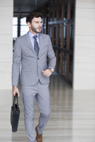 Confident businessman walking with briefcase