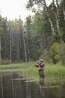 middle-aged man casting his fly fishing rod