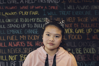 Portrait serious, confident Asian tween girl wearing cat headband against wall with chalk text