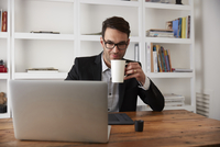 Businessman holding coffee mug while using laptop at table in home office
