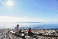 Older woman and child sitting on a rocky beach on a sunny day.