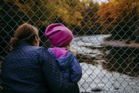 grandmother and granddaughter on a bridge looking at the river fall