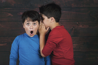 Boy Whispering In Surprised Friend Ear While Standing Against Wooden Wall