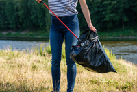 Midsection Of Woman Collecting Garbage On Land Against River 11115173243| 写真素材・ストックフォト・画像・イラスト素材|アマナイメージズ
